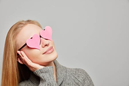 Young woman daydreaming with hearts on her eyes looking up Stock Photo