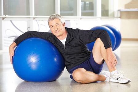 gym ball: Happy senior man with gym ball in fitness center doing back training Stock Photo