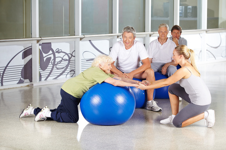 gym ball: Fitness instructor helping senior woman with gym ball in rehab center Stock Photo
