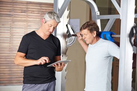 muscle formation: Senior man weightlifting barbell with personal trainer holding tablet computer