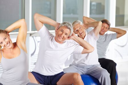 muscle formation: Happy senior group doing back training on gym balls in fitness center Stock Photo