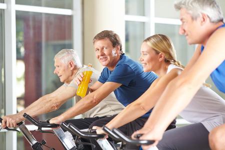 sediento: Hombre sediento de beber refresco en bicicleta de spinning en un gimnasio Foto de archivo