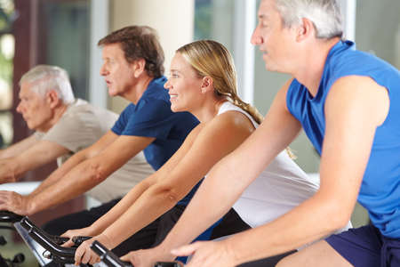 trainer device: Happy senior people group exercising in spinning class in gym