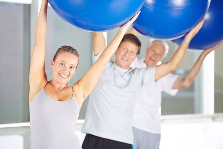 gym ball: Group of senior people doing back training with gym ball in fitness center