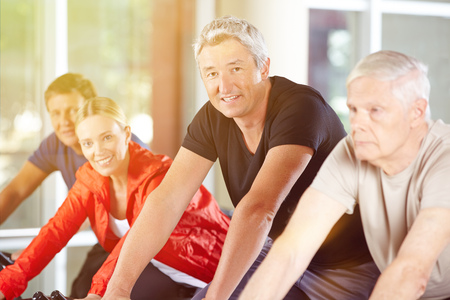 home trainer: Happy senior group together in a spinning class in gym Stock Photo