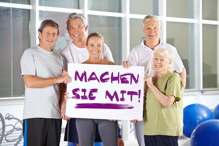 Group of senior people holding sign saying German slogan