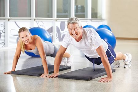 Man and woman doing push ups together in a gym photo