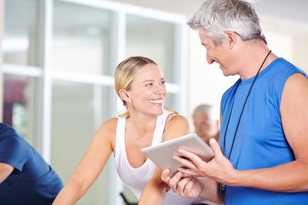 muscle formation: Fitness trainer with tablet PC talking to smiling woman in a gym