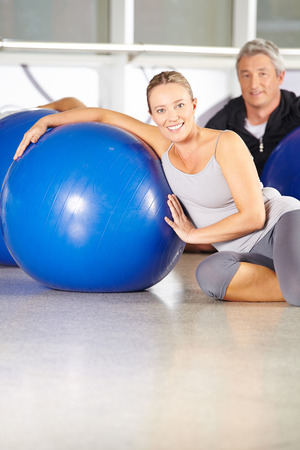 Senior couple sitting with gym ball in a fitness center photo