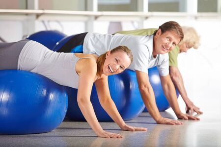 health club: Happy senior group doing back training in health club on gym ball Stock Photo