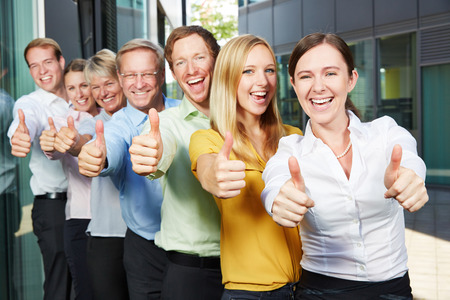 Cheering business people team holding thumbs up next to the office