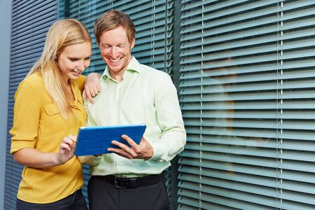 pc: Man and woman looking together at a website on a tablet PC Stock Photo