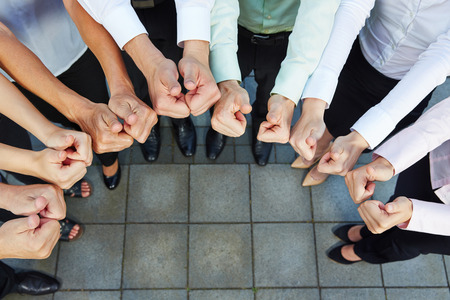 semicircle: Business team holding many thumbs up in a semicircle from above