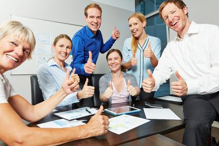 congratulations: El animar del asunto que sostienen muchos pulgar hacia arriba en la oficina durante una reunión
