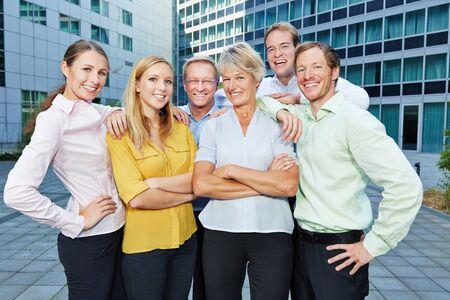 Los empleados felices y sonrientes miembros del personal como un equipo de negocios exitoso