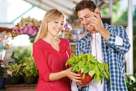 garden staff: Woman and man standing with a green plant (philodendron cordatum) in a nursery shop