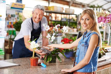 Vrouw met behulp van mobiele betalingen met smartphone in een ijzerhandel