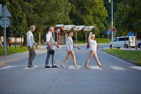 paso de peatones: Happy group of seniors walking over crosswalk in a line Foto de archivo