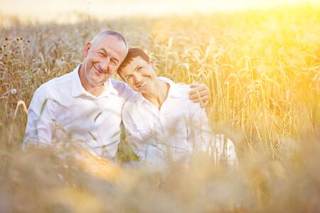 happy senior: Happy senior couple on summer vacation sitting in a wheat field Stock Photo