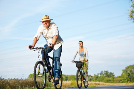 couple nature: Senior couple cycling with bikes in nature in summer Stock Photo