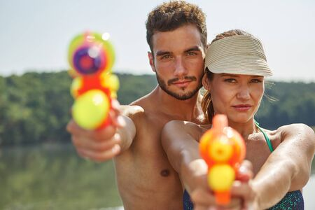 refreshment: Couple aiming with squirt guns in summer on their holidays
