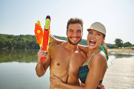 squirt: Happy couple at a lake with squirt guns having fun and laughing