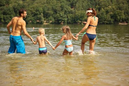 personas banandose: Familia con los niños que se bañan en verano en el lago Foto de archivo