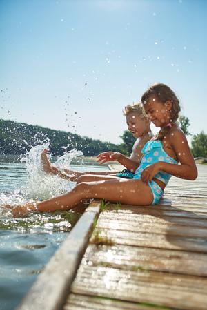 niños nadando: Dos niños que salpican el agua con sus pies en verano