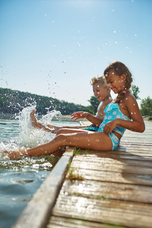 Two children splashing the water with their feet in summer