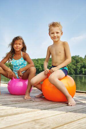 Twee kinderen die met een spacehooper bij een meer in de zomer Stockfoto