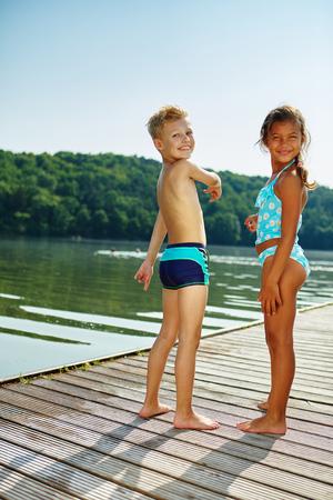 Twee kinderen staande op een steiger aan het meer in de zomer