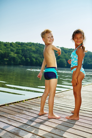 brothers: Two children standing on a pier at the lake in summer