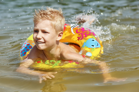 young boys: Kid with a floating ring having funand splashing in the lake