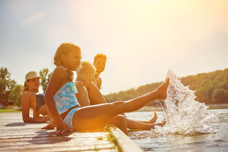 Family splashing water at a lake on their summer holidays Banque d'images