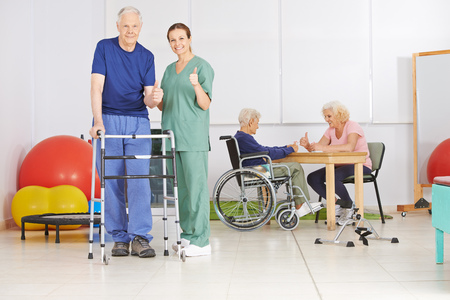 ancianos felices: anciano y enfermera geriátrica que detienen los pulgares juntos en un hogar de ancianos Foto de archivo