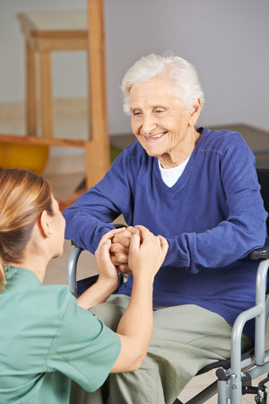 geriatric nurse: Happy senior woman in wheelchair holding hands with geriatric nurse Stock Photo