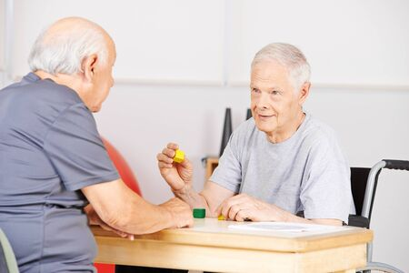demented: Two demented senior men in nursing home talking to each other and playing with building bricks