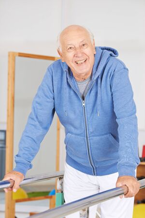 old man standing: Old man standing on handle in physiotherapy Stock Photo