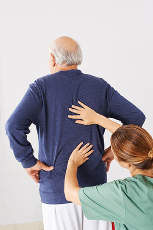 pangs: Physiotherapist laying hands on senior man with back pain in physical therapy