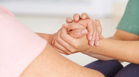 with sympathy: Geriatric nurse holding hands of senior woman for consolation