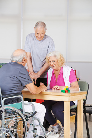 nursing allowance: Happy senior people during rehab playing Bingo together Stock Photo