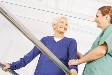 senior exercise: Smiling old woman in physiotherapy on a treadmill with physiotherapist