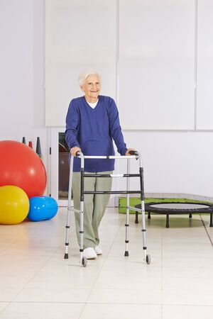 mobility nursing: Happy senior woman with walker exercising walking in physiotherapy