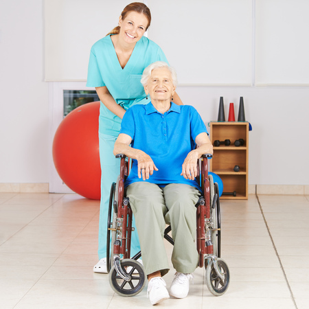 geriatric nurse: Geriatric nurse with old woman in wheelchair at physiotherapy Stock Photo