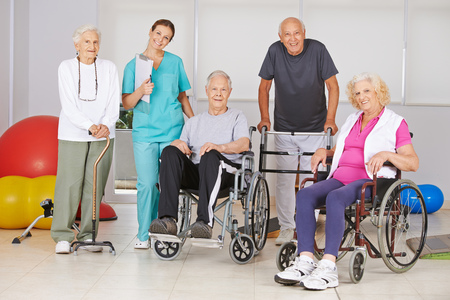 geriatric nurse: Group of happy senior people at physiotherapy in a nursing home with geriatric nurse Stock Photo