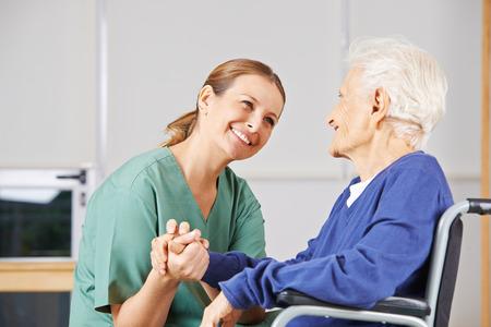 Gelukkig geriatrisch verpleegkundige hand in hand met een senior vrouw in een rolstoel
