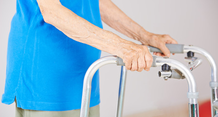 nursing allowance: Hands of an old woman an a walker for support