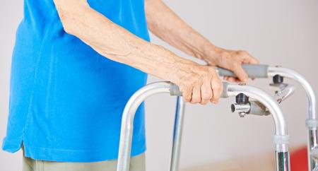care allowance: Hands of an old woman an a walker for support