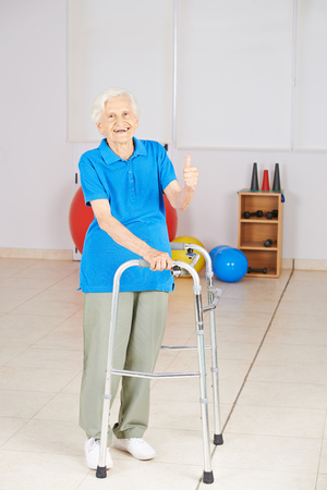 mujeres ancianas: mujer feliz de edad con andador que detiene sus pulgares Foto de archivo