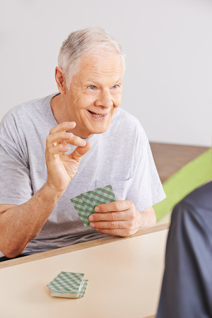 skat: Two happy senior men playing cards together in a nursing home